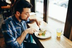 Jeune homme beau prenant le déjeuner dans seul le restaurant confortable Photos stock