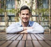 Jeune homme beau reposant les bras croisés sur la surface en bois Image libre de droits