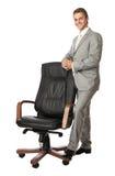 Jeune homme beau restant à côté d'un fauteuil Photo stock