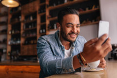 Jeune homme beau s'asseyant au café faisant l'appel visuel Photo libre de droits