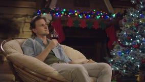 Jeune homme beau s'asseyant avec un verre de vin dans la nuit de nouvelle année par l'arbre décoré banque de vidéos