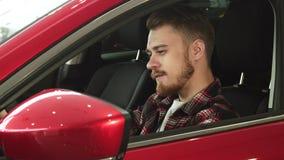 Jeune homme beau s'asseyant confortablement dans sa nouvelle voiture souriant à l'appareil-photo banque de vidéos