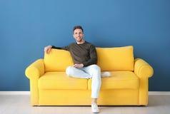 Jeune homme beau s'asseyant sur le sofa, photos libres de droits