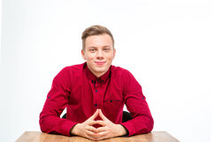 Jeune homme beau satisfait dans la séance et le sourire rouges de chemise Images libres de droits