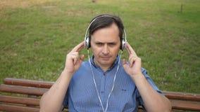 Jeune homme beau se reposant en parc écoutant la musique de son smartphone avec des écouteurs et dansant dehors dans a banque de vidéos