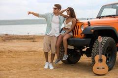 Jeune homme beau se tenant avec son amie près de sa voiture Images libres de droits