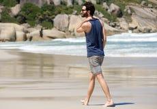 Jeune homme beau seul marchant sur la plage vide Photographie stock