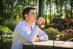 Jeune homme beau seul s'asseyant à la table dehors photos stock