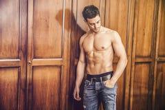Jeune homme beau sexy se tenant sans chemise contre la garde-robe photo stock