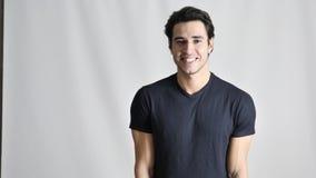 Jeune homme beau souriant à l'appareil-photo banque de vidéos