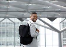 Jeune homme beau souriant avec le sac à l'aéroport Images stock