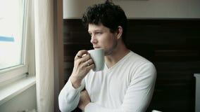 Jeune homme beau sur la cuisine avec la tasse dans des mains clips vidéos