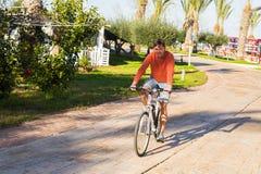 Jeune homme beau sur le vélo en parc Bicyclette, loisirs et concept de personnes Images stock