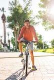 Jeune homme beau sur le vélo en parc Bicyclette, loisirs et concept de personnes Image libre de droits