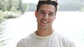 Jeune homme beau sur un rivage ou une rivière du ` s de lac banque de vidéos