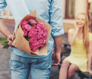 Jeune homme beau tenant des fleurs derrière le sien de retour Images stock