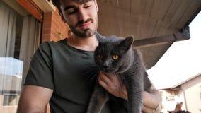 Jeune homme beau tenant son animal familier gris de chat Photo libre de droits