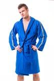 Jeune homme beau utilisant le peignoir bleu, d'isolement Photos libres de droits