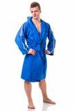 Jeune homme beau utilisant le peignoir bleu, d'isolement Photo libre de droits