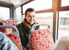Jeune homme beau voyageant en autobus, ayant l'amusement Image stock