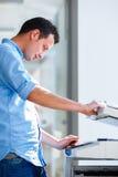 Jeune homme bel à l'aide d'une machine de copie photo stock