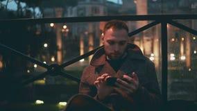 Jeune homme bel à l'aide du smartphone, égalisant la ville sur un fond L'homme passent en revue l'Internet avec la technologie d' Images stock