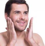 Jeune homme bel appliquant la lotion. Photo libre de droits
