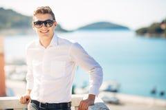 Jeune homme bel appréciant le sejour à l'hôtel de lieu de villégiature luxueux avec la vue panoramique sur la mer Homme gai de so photo libre de droits