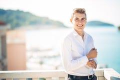 Jeune homme bel appréciant le sejour à l'hôtel de lieu de villégiature luxueux avec la vue panoramique sur la mer Homme gai de so images stock