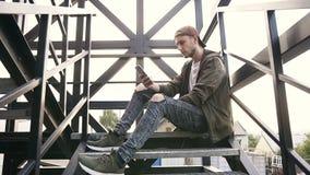 Jeune homme bel avec le smartphone se reposant aux escaliers de fer Garçon adolescent de hippie employant le wifi de smartphone r banque de vidéos