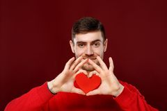 Jeune homme bel avec un coeur rouge dans des ses mains le Saint Valentin Photo stock