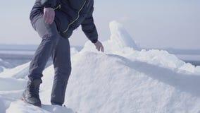 Jeune homme bel barbu dans la veste, le chapeau chaud et les bottes climbling le glacier Nature stupéfiante d'un glacier neigeux  clips vidéos