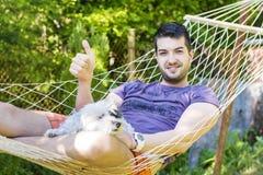 Jeune homme bel détendant dans l'hamac avec son chien Photographie stock libre de droits