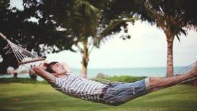 Jeune homme bel détendant sur l'hamac sur la belle plage tropicale Concept de vacances 1920x1080 clips vidéos