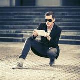 Jeune homme bel d'affaires à l'aide de la tablette numérique dans la rue de ville Photo stock