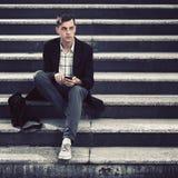 Jeune homme bel d'affaires à l'aide du téléphone intelligent sur les étapes Photos libres de droits