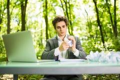 Jeune homme bel d'affaires au bureau de table de travail avec l'ordinateur portable dans la forêt verte avec le blanc chiffonné d Images stock