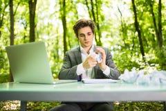 Jeune homme bel d'affaires au bureau de table de travail avec l'ordinateur portable dans la forêt verte avec le blanc chiffonné d Photo stock