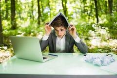 Jeune homme bel d'affaires au bureau de table de travail avec l'ordinateur portable dans la forêt verte avec le carnet aérien, tr Image stock