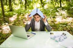 Jeune homme bel d'affaires au bureau de table de travail avec l'ordinateur portable dans la forêt verte avec le carnet aérien, tr Photos libres de droits