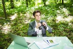 Jeune homme bel d'affaires au bureau de table de travail avec l'ordinateur portable dans la forêt verte avec les concurrents de r Photo stock