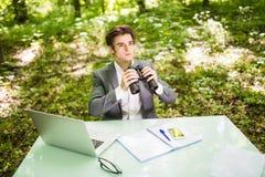 Jeune homme bel d'affaires au bureau de table de travail avec l'ordinateur portable dans la forêt verte avec les concurrents de r Image stock