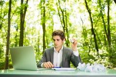 Jeune homme bel d'affaires au bureau de table de travail avec l'ordinateur portable dans la forêt verte avec les papiers chiffonn Images libres de droits