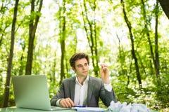 Jeune homme bel d'affaires au bureau de table de travail avec l'ordinateur portable dans la forêt verte avec les papiers chiffonn Photo libre de droits