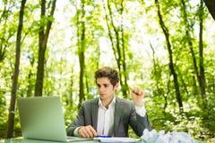 Jeune homme bel d'affaires au bureau de table de travail avec l'ordinateur portable dans la forêt verte avec les papiers chiffonn Photographie stock