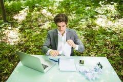 Jeune homme bel d'affaires au bureau de table de travail avec l'ordinateur portable en journal de travail vert de larme de forêt  Photographie stock libre de droits