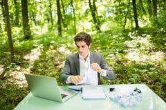 Jeune homme bel d'affaires au bureau de table de travail avec l'ordinateur portable en journal de travail vert de larme de forêt  Photographie stock