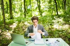 Jeune homme bel d'affaires au bureau de table de travail avec l'ordinateur portable en journal de travail vert de larme de forêt  Photo stock