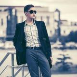 Jeune homme bel d'affaires dans des lunettes de soleil dans la rue de ville photos stock