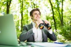 Jeune homme bel d'affaires de sourire au bureau de table de travail avec l'ordinateur portable dans la forêt verte avec les concu Photographie stock